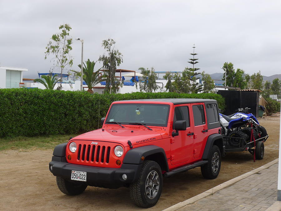 front and side view of a mint condition red color jeep wrangler rubicon with 4 0 l engine and a black vehicle top parked with two quadbikes in a Customed Jeep Wrangler Side View