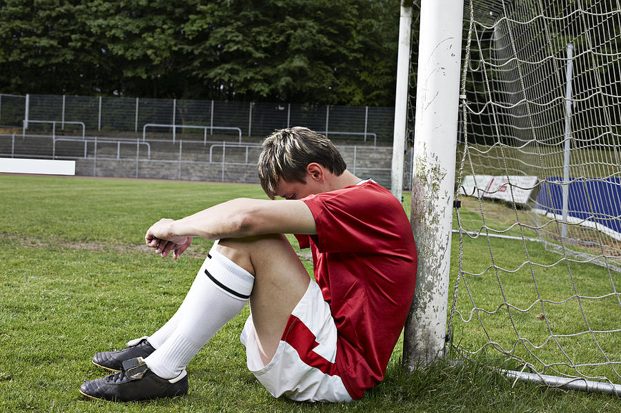 Frustrated soccer player on field Photograph by Westend61