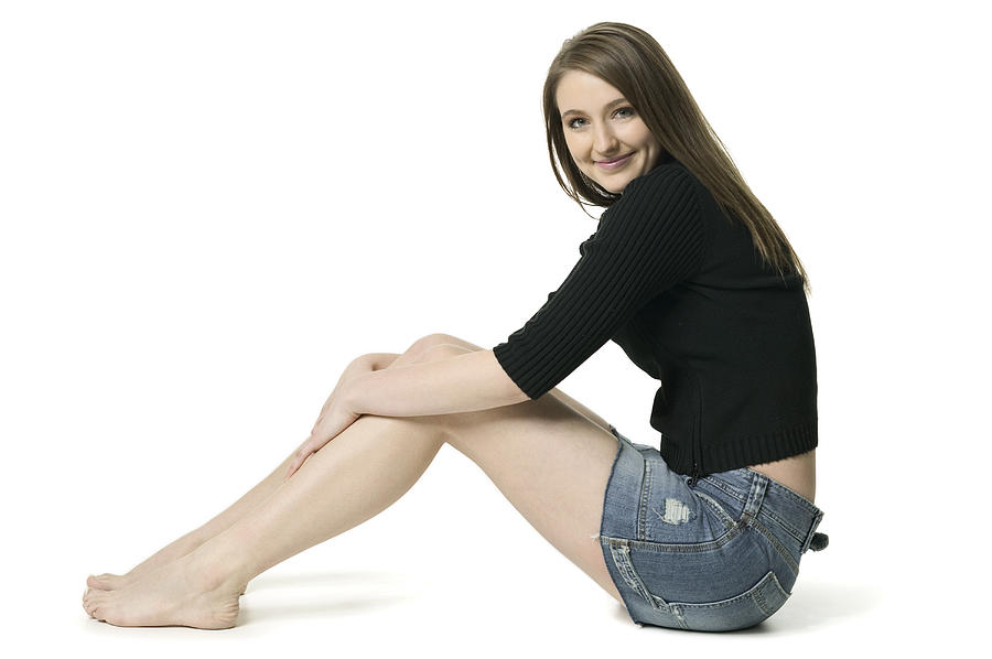 Full Body Shot Of A Teenage Brunette Female In A Black Sweater As She Sits And Smiles Photograph by Photodisc