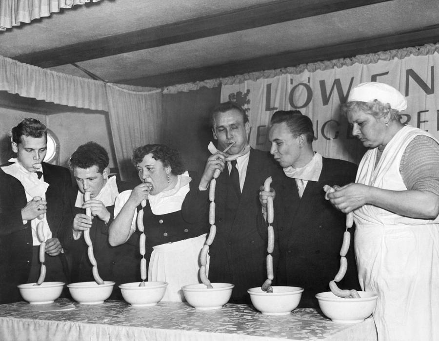 Alcohol Photograph - German Sausage Eating Contest by Underwood Archives