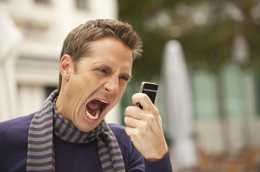 Germany, Bavaria, Munich, Man screaming into mobile phone Photograph by Westend61