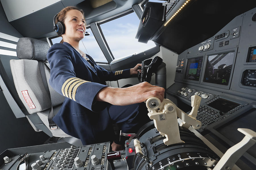 Germany, Bavaria, Munich, Woman Flight Captain Piloting Aeroplane From Airplane Cockpit Photograph by Westend61
