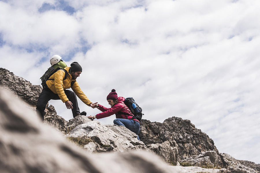 Germany, Bavaria, Oberstdorf, Man Helping Woman Climbing Up Rock Photograph by Westend61