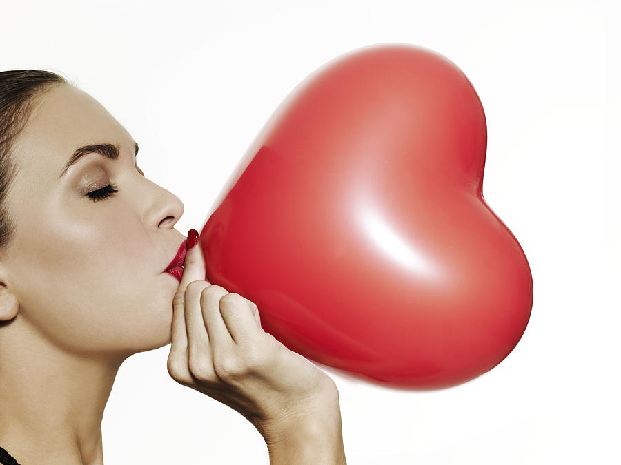 Girl Blowing Up A Red Heart Shaped Balloon Photograph by Elizabeth Hachem