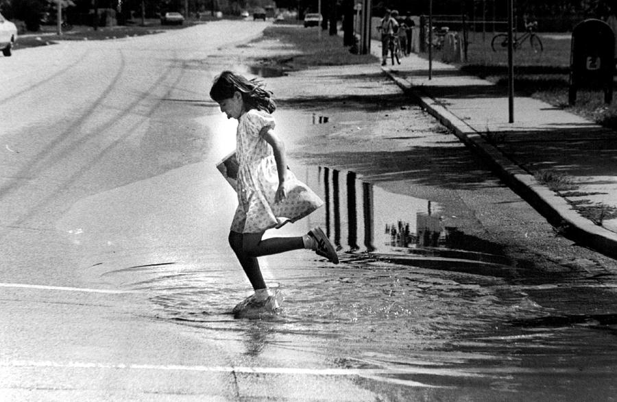 Rare Photograph - Girl Playing In A Puddle by Retro Images Archive