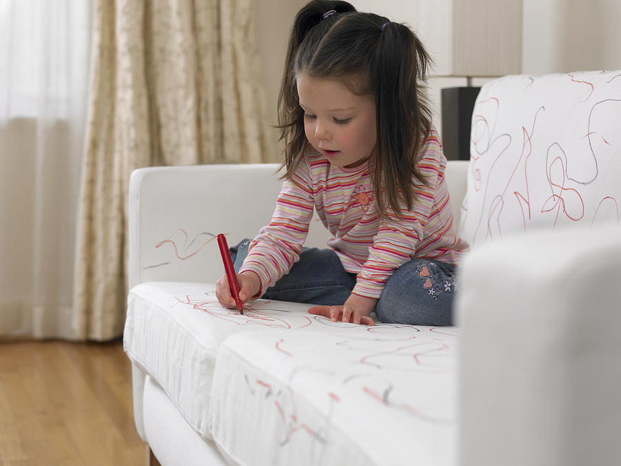 Girl using marker on sofa Photograph by Adam Gault