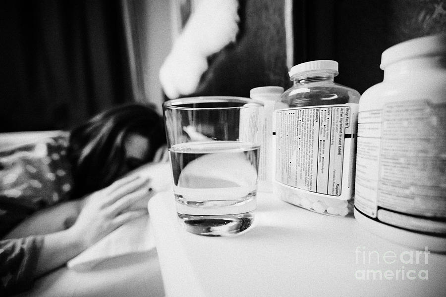 Glass Photograph - Glass Of Water And Bottles Of Pills On Bedside Table Of Early Twenties Woman In Bed In A Bedroom by Joe Fox