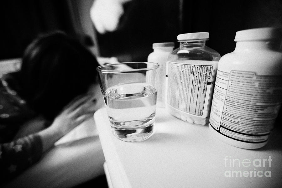 Glass Photograph - Glass Of Water And Bottles Of Pills On Bedside Table Of Early Twenties Woman Waking In Bed In A Bedr by Joe Fox