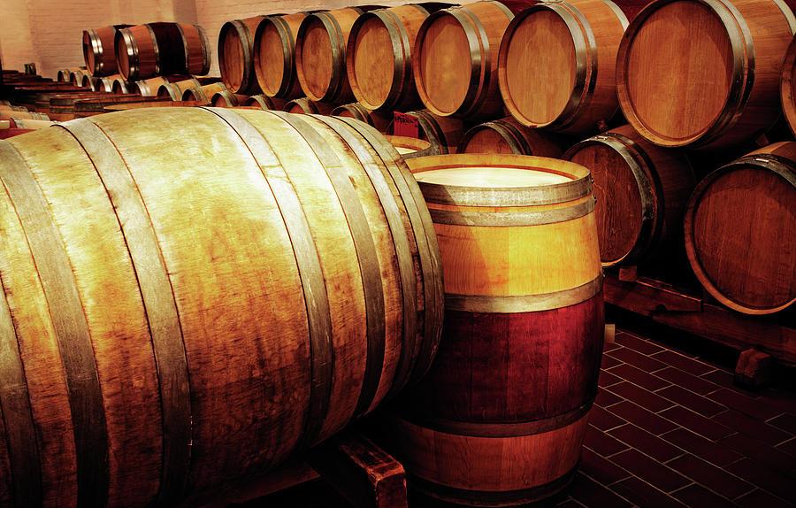 Golden Oak Wine Barrels Glow In Winery Photograph by Rapideye