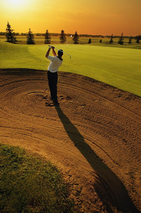 Golfer Taking A Swing From A Golf Bunker Photograph By