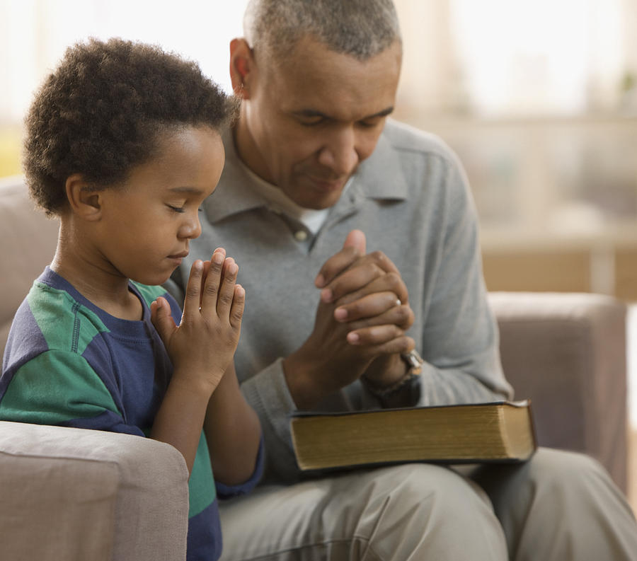Grandfather and grandson praying together Photograph by Jose Luis Pelaez Inc