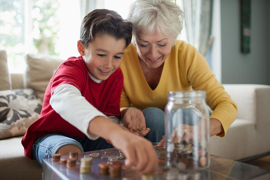 Grandmother and grandson counting coins Photograph by Paul Bradbury