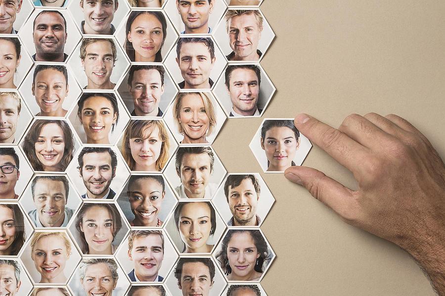Grid of hexagonal portraits, hand adding new one Photograph by Dimitri Otis