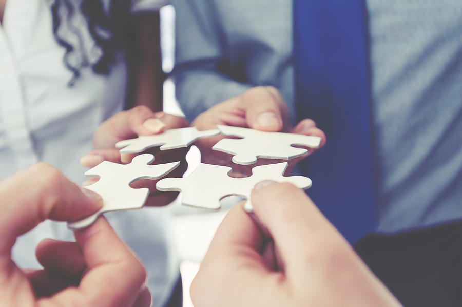 Group of business people holding a jigsaw puzzle pieces. Photograph by Courtneyk