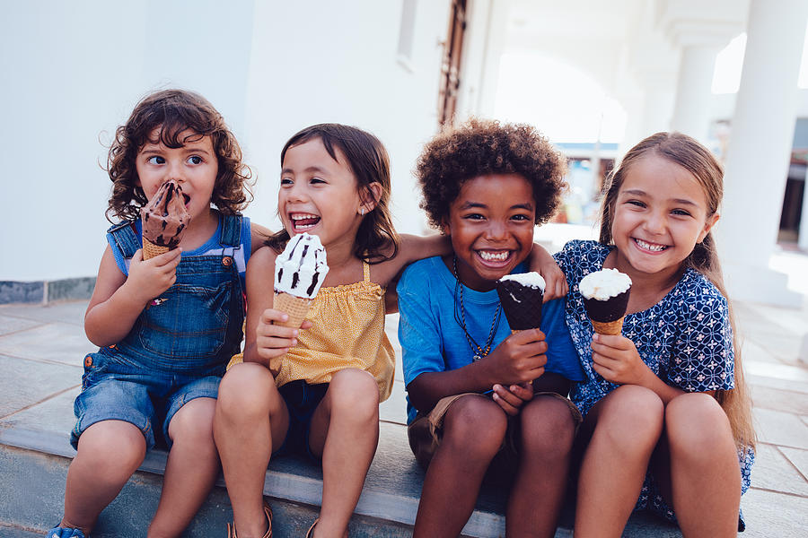 Group of cheerful multi-ethnic children eating ice-cream in summer Photograph by Wundervisuals