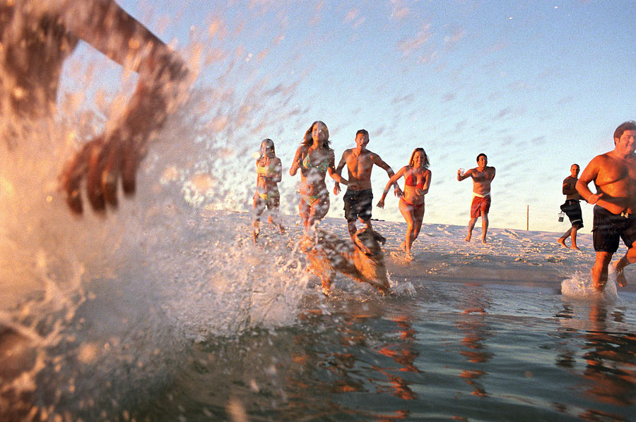 Group Of Young Adults Running Through Water At Oceans Shore Photograph by Sean Murphy