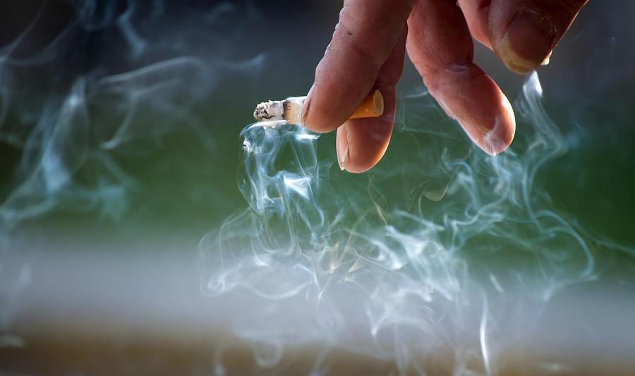Hand Holding Burning Cigarette Photograph by Luis Diaz Devesa