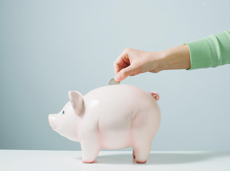 Hand placing coin in piggy bank Photograph by PM Images