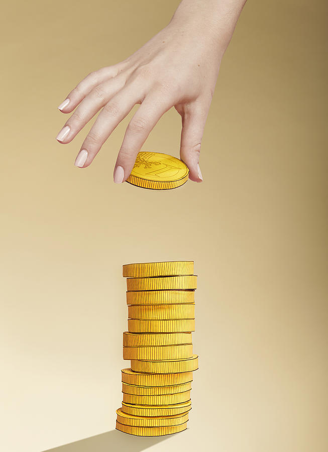 Hand putting paper gold coin on stack of coins Photograph by Paper Boat Creative