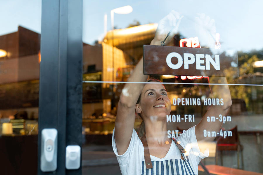 Happy business owner hanging an open sign at a cafe Photograph by Andresr