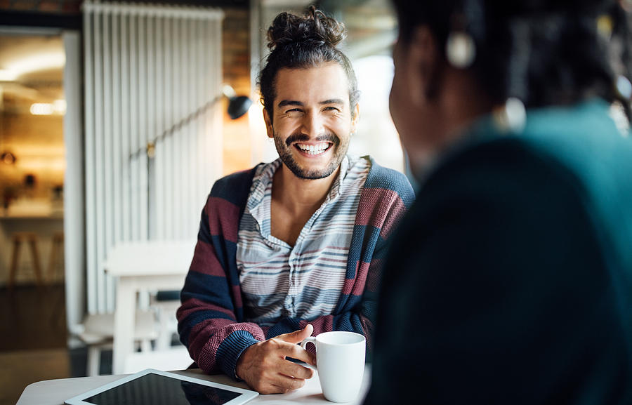 Happy businessman having coffee with colleague Photograph by Luis Alvarez