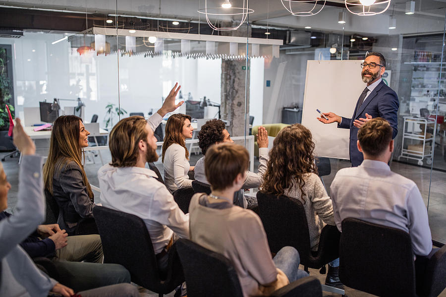 Happy CEO giving his team a business presentation in a board room. Photograph by Skynesher