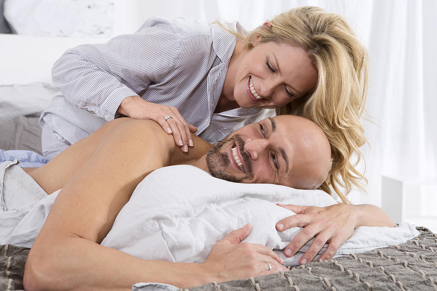 Happy Couple In Bedroom, Woman Giving Man A Back Massage Photograph by  Westend61