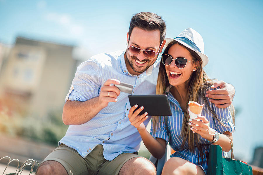 Happy couple paying on line with credit card and digital tablet on the street Photograph by Jovanmandic