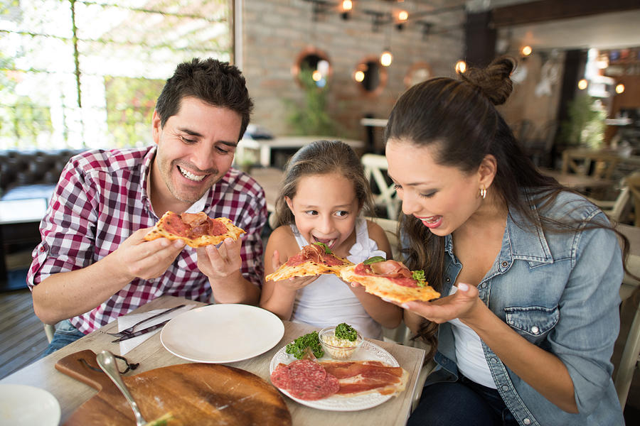 Happy family eating pizza at a restaurant Photograph by Andresr