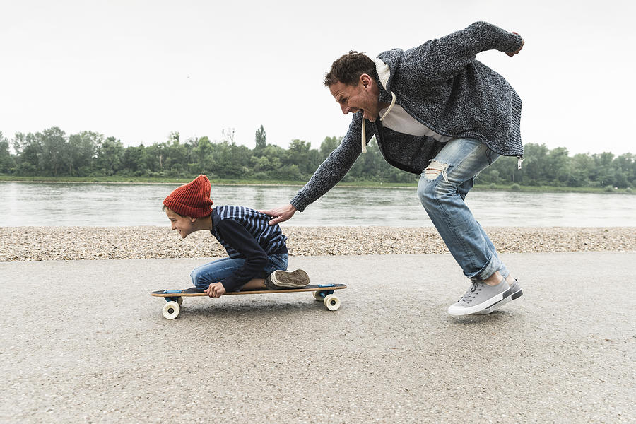 Happy father pushing son on skateboard at the riverside Photograph by Westend61