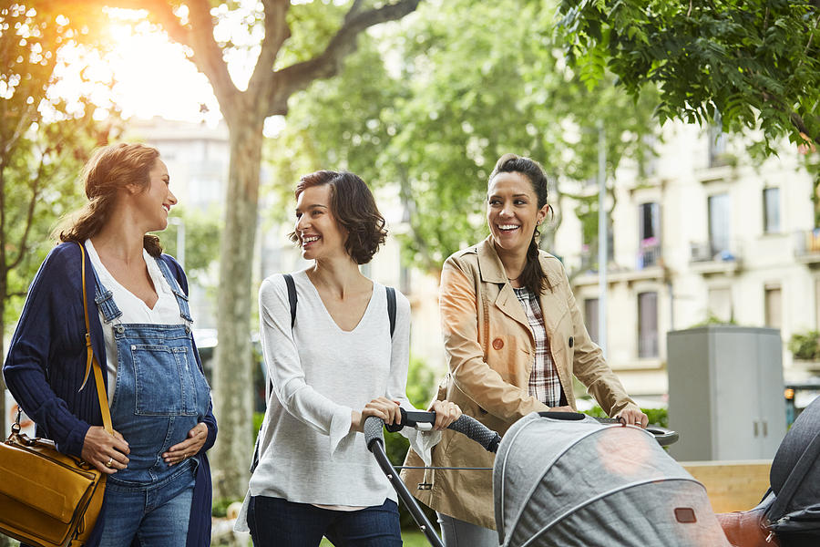 Happy Pregnant Woman With Friends In Park Photograph by Morsa Images