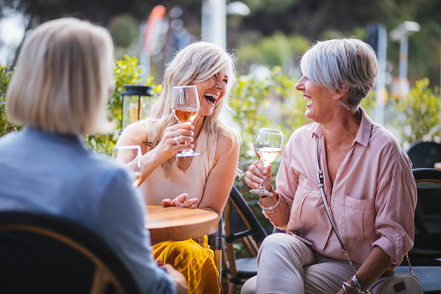 Happy senior women drinking wine and laughing together at restaurant Photograph by Wundervisuals