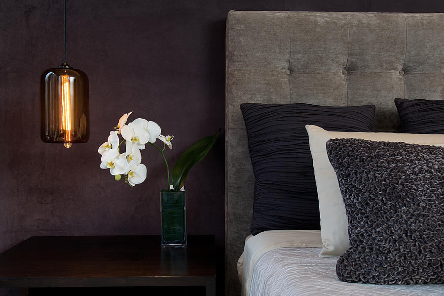 Headboard Detail With Pillows Lamp And Orchid Flowers Photograph by FlashSG
