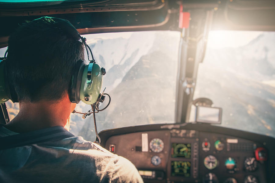 Helicopter cockpit with rear view of unrecognizable men co-pilot flying over Mont Blanc massif in French Alps mountains at sunset Photograph by Gregory_DUBUS