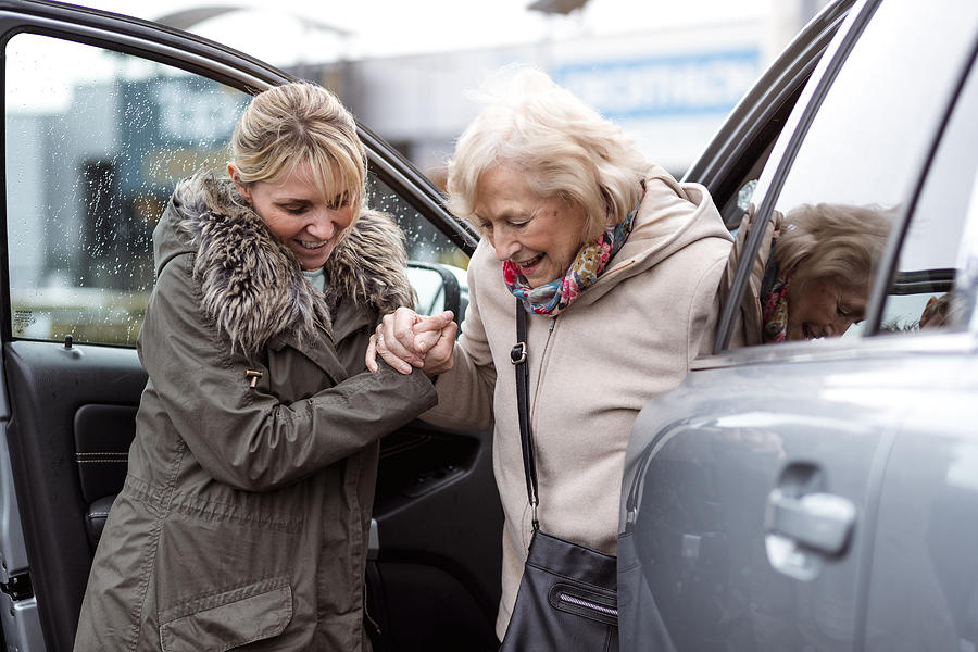 Helping a Senior Woman Out of the Car Photograph by SolStock