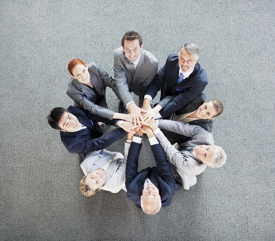 High angle view portrait of business people joining hands in circle Photograph by Robert Daly