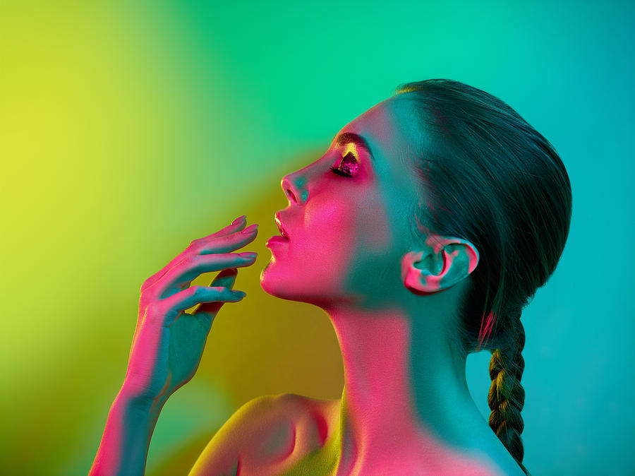 High Fashion model woman in colorful bright lights posing in studio Photograph by Anton5146