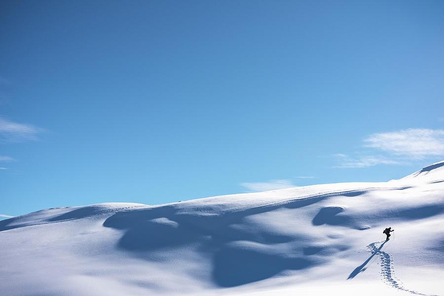 Hiker Walking Up Snowy Hillside Photograph by Deimagine