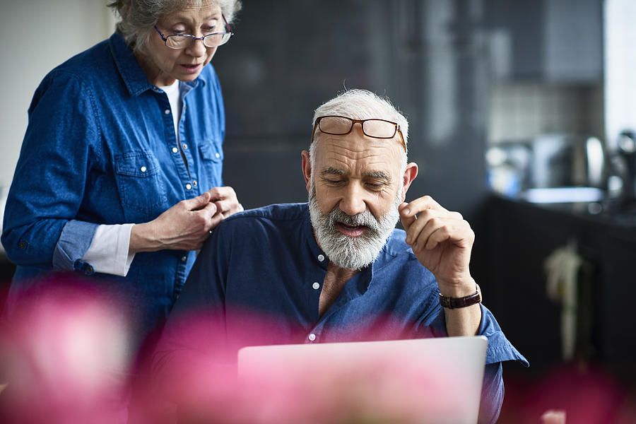 Hipster senior man with beard using laptop and woman watching Photograph by 10000 Hours