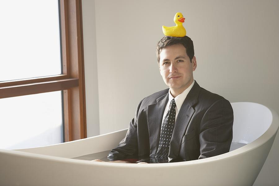 Hispanic businessman sitting in a bathtub with a rubber ducky on his head Photograph by Ariel Skelley
