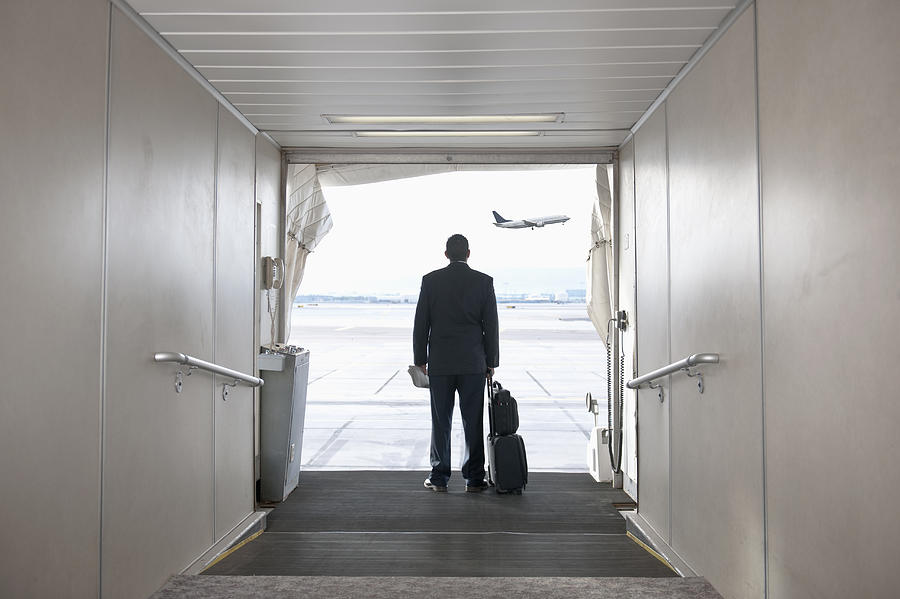 Hispanic businessman standing on jetway Photograph by Jacobs Stock Photography Ltd