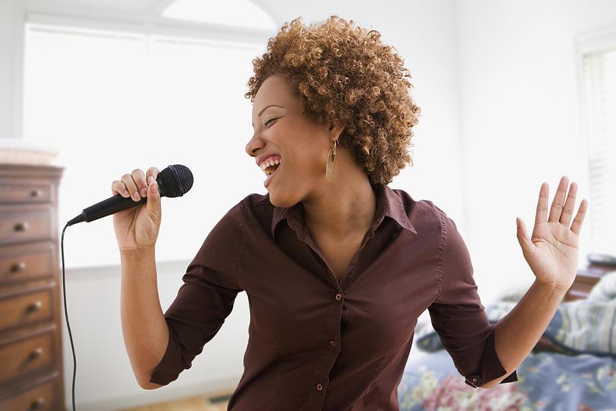 Hispanic woman singing on microphone in bedroom Photograph by Jose Luis Pelaez Inc