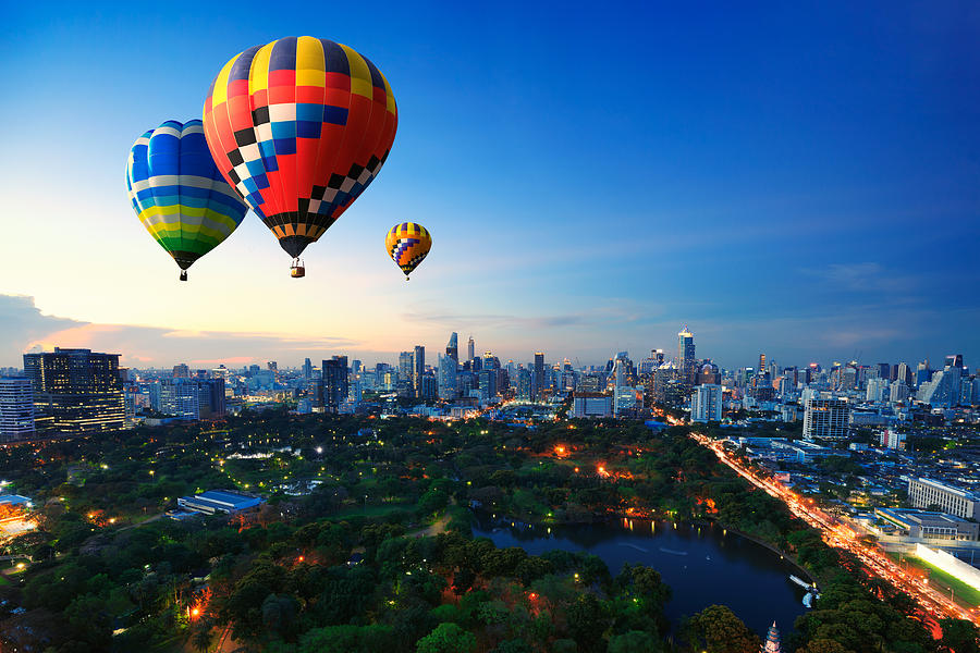 Hot Air Balloons Fly Over Cityscape At Sunset Background Photograph by Busakorn Pongparnit