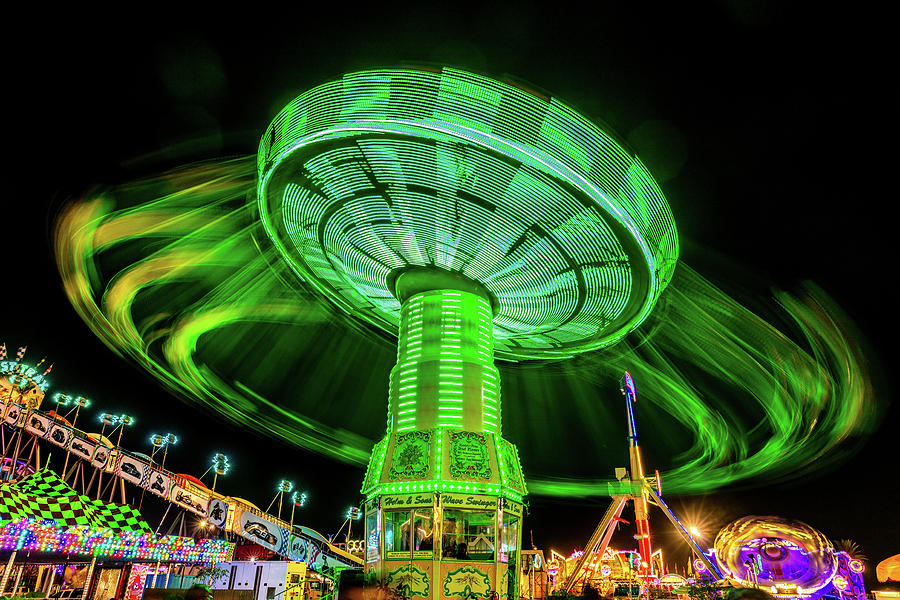 Horizontal Photograph - Illuminated Fair Ride With Blurred Neon by Panoramic Images