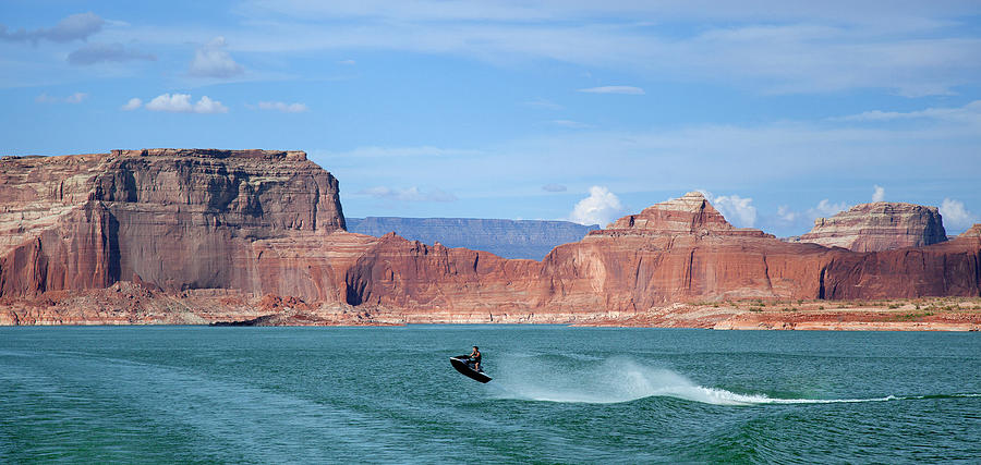 Jet Ski With Red Rock Formations Beyond Photograph by Timothy Hearsum