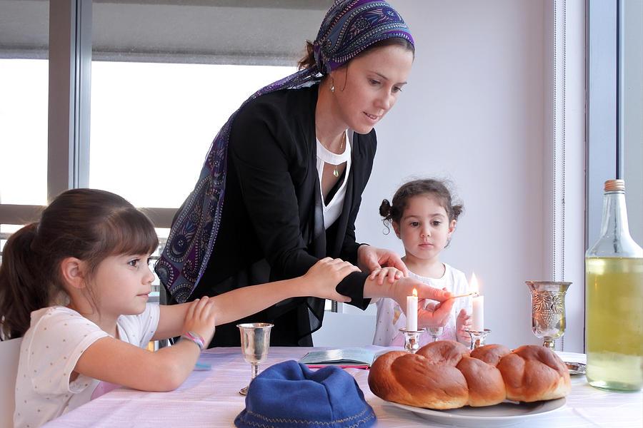 Jewish mother and daughters light Sabbath candles Photograph by Rafael Ben-Ari