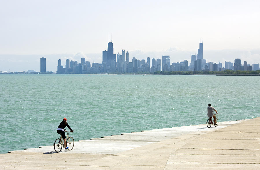 Lake Michigan with skyline and bicyclers Photograph by by Ken Ilio