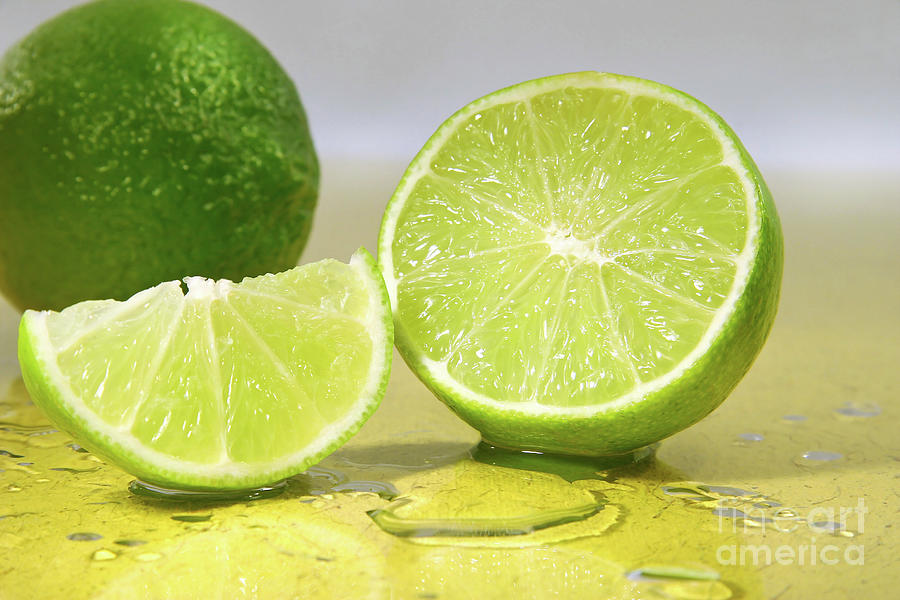 Bitter Photograph - Limes On Yellow Surface by Sandra Cunningham