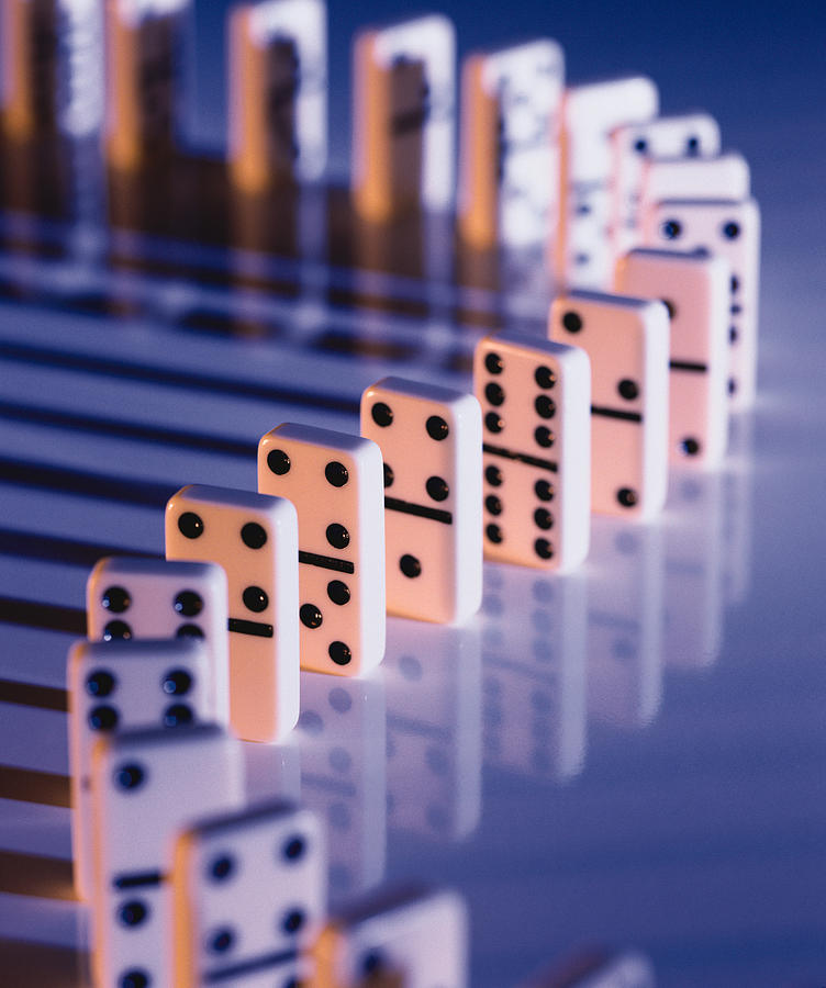 Lined Up Dominoes On A Blue Surface Create Long Shadows Photograph by Photodisc