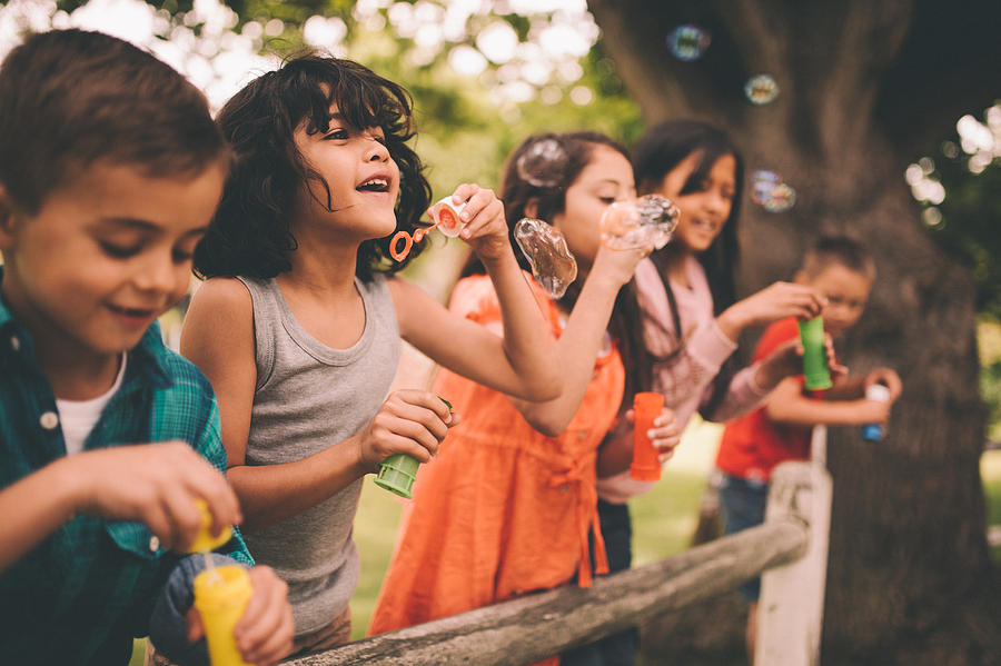 Little boy having fun with friends in park blowing bubbles Photograph by Wundervisuals